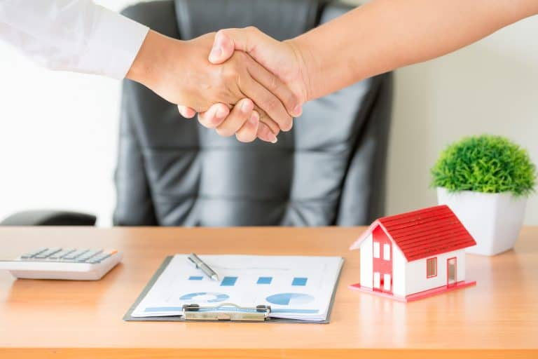 hands of agent and client shaking hands after signed contract to rent an apartment.